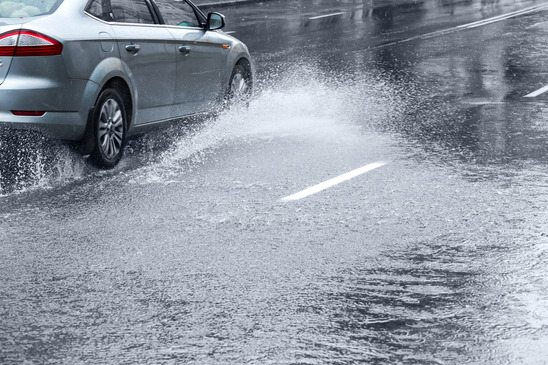 Car driving on huge puddle during a downpour