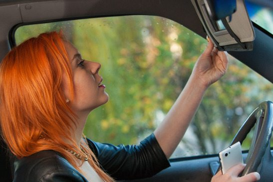 girl using phone looking at mirror while driving the car.